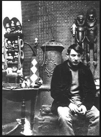 Picasso dans son atelier du Bateau- Lavoir. Derrière lui à droite des masques africains: ils auront une influence extraordinaire dans sa peinture qui débouchera sur le cubisme.  Cet atelier n'existe plus car il a brûlé en 1970.
